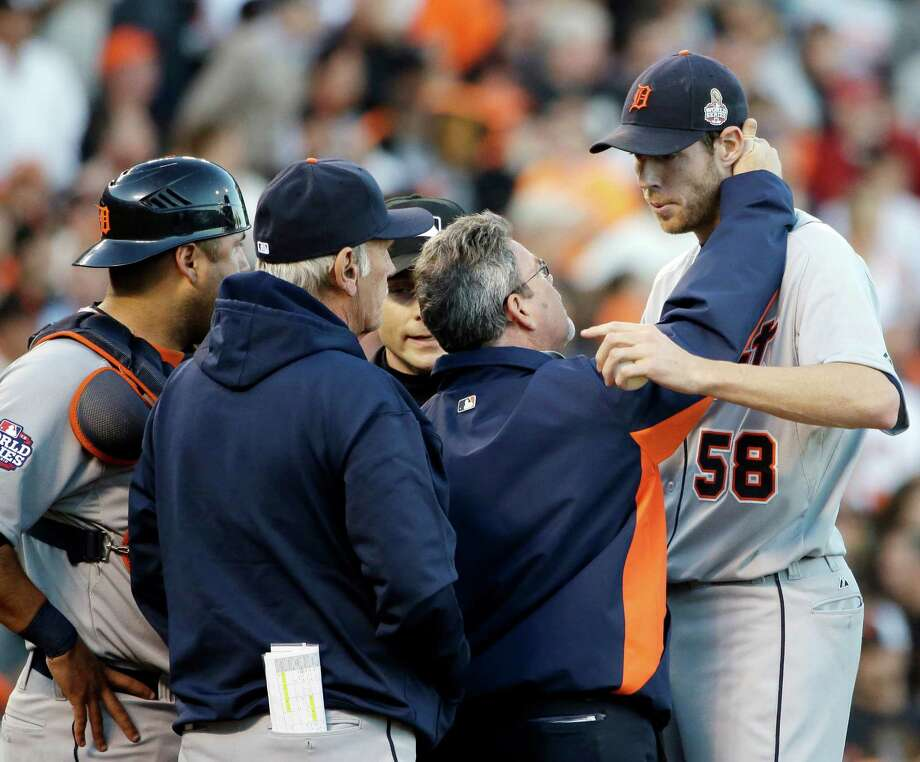 Tigers manager Jim Leyland, left, looks on as a trainer checks Doug Fister, who was hit by a line drive. Photo: David J. Phillip, STF / AP