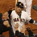 Giants' right fielder Hunter Pence is greeted at the dugout after hitting a sacrifice in the 8th to score Angel Pagan during game 2 of the World Series at AT&T Park on Thursday, Oct. 25, 2012 in San Francisco, Calif.