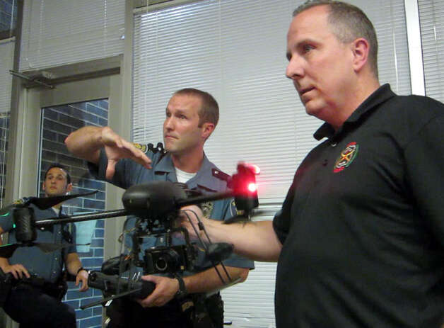 Seattle Police displayed a drone that has the ability to take aerial photos at a maximum of 400 feet. It can run for about 10 minutes. The plan has received mixed reviews, and at an Oct. 25 meeting at the Garfield Community Center several people responded to police by yelling and swearing. At left is Jim Britt, who on Oct. 19 was awarded the SPD Lifesaving Award for helping save a 16-year-old from drowning near the Leschi marina. Photo: Casey McNerthney/seattlepi.com