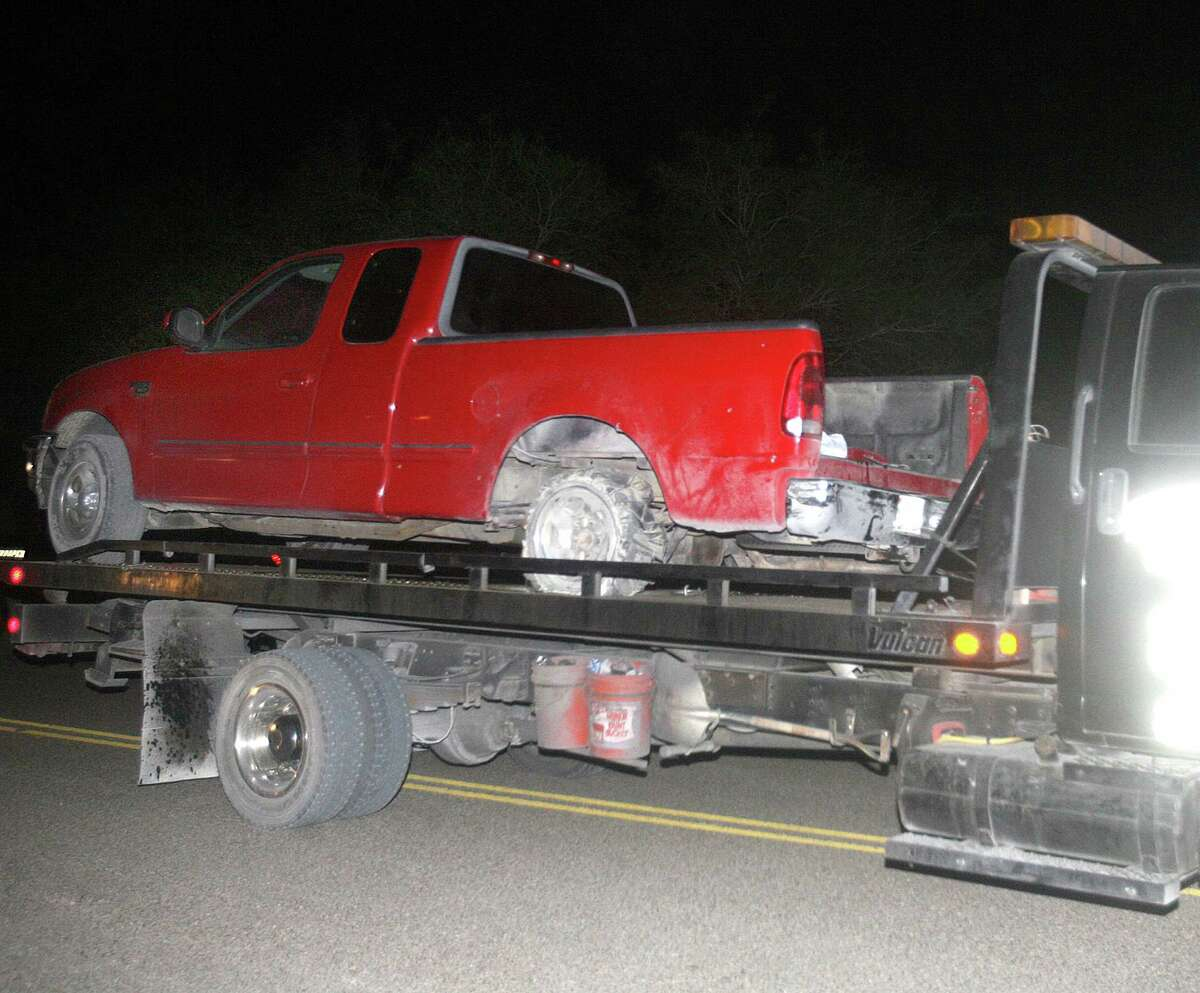 A red pickup truck is moved from the scene after a chase between law enforcement and suspected human smugglers on 7 mile road north of La Joya, Thursday, Oct. 25, 2012. Texas Department of Public Safety sharpshooter opened fire on an evading vehicle loaded with suspected illegal immigrants, leaving at least two people dead, sources familiar with the investigation said.