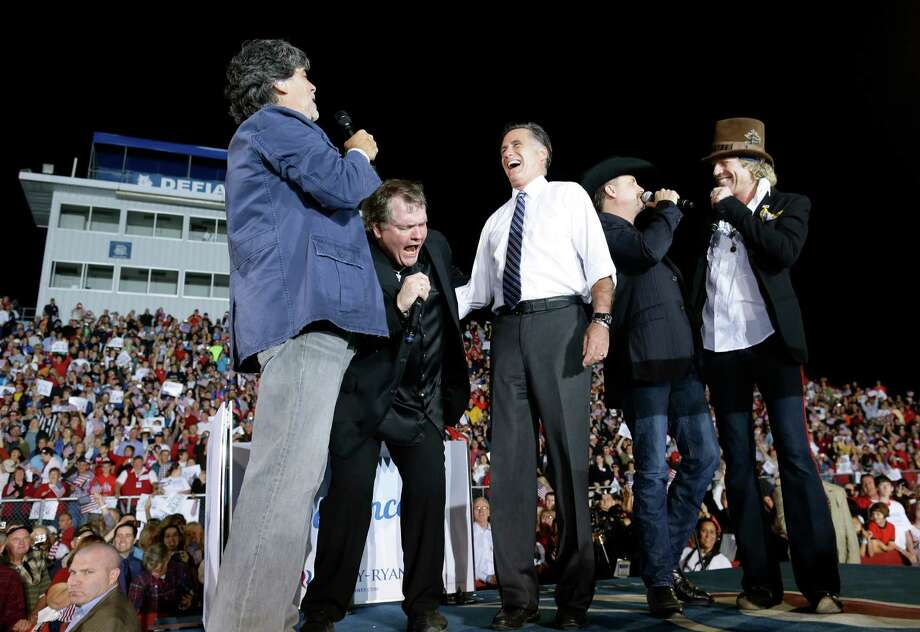 """Republican presidential candidate and former Massachusetts Gov. Mitt Romney sings """"God Bless America"""" as he campaigns at the football stadium at Defiance High School in Defiance, Ohio, Thursday, Oct. 25, 2012, with from left to right, Randy Owen, Meat Loaf, John Rich and Big Kenny. (AP Photo/Charles Dharapak) Photo: Charles Dharapak"""