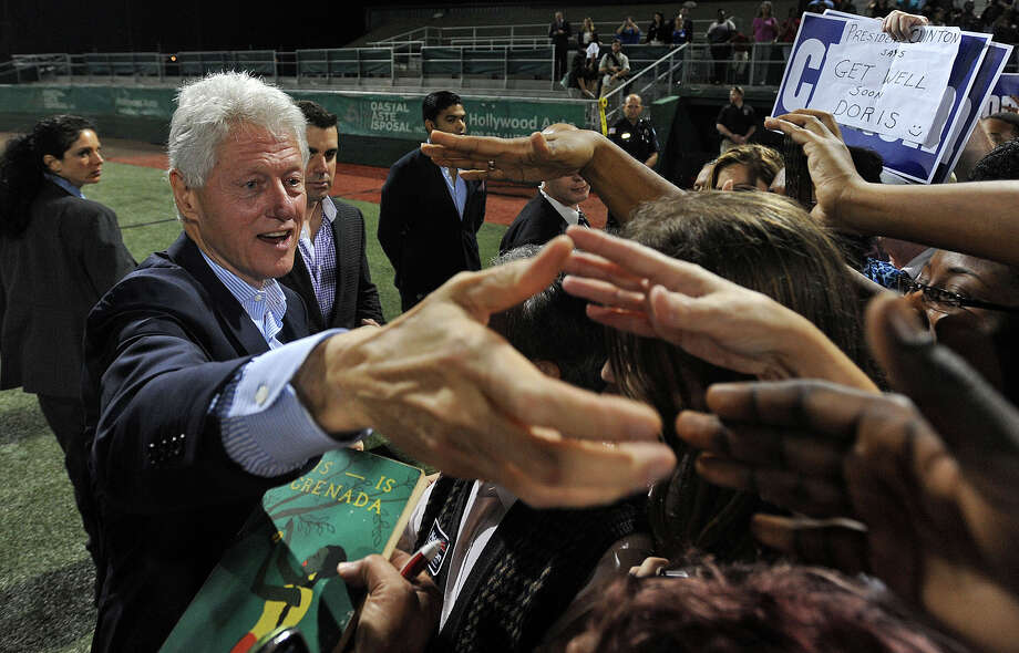 After speaking on issues of school tuition, Medicare and national debt, Bill Clinton reached into the crowd to shake hands and give autographs at Vincent-Beck Stadium on Thursday. Photo taken Thursday, October 25, 2012 Guiseppe Barranco/The Enterprise Photo: Guiseppe Barranco, STAFF PHOTOGRAPHER / The Beaumont Enterprise