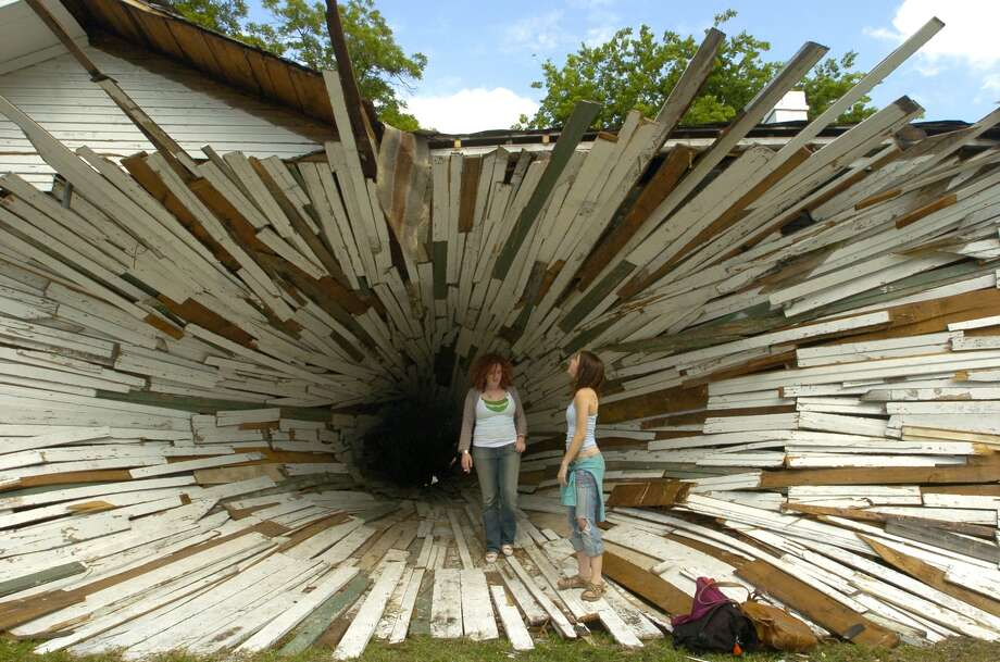 "Lindsey Hardin, left, and Samantha Santoski walk through ""inversion"", a sculpture by Dan Havel and Dean Ruck, Wednesday, May 4, 2005, in Houston. Havel and Ruck are transforming two Art League houses into a funnel-like vortex between two houses, where the exterior skin of the home will be peeled back beginning on the west wall and narrowed into a narrowing spiral that ends on the east wall. (Photo by Brett Coomer/Houston Chronicle)"