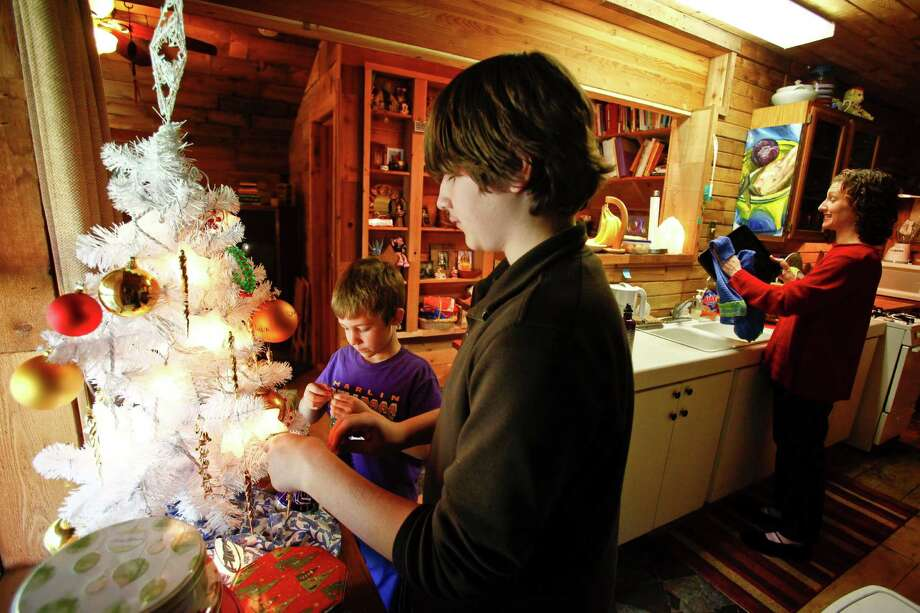 Kristie Stevens' children, Joseph Chamrad, 7, (left) and Zachary Chamrad, 13, decorate the family Christmas tree at their home Wednesday, Dec. 9, 2009, in Huntsville.  The house was built by Dan Phillips using recycled materials then sold to Stevens for $10.
