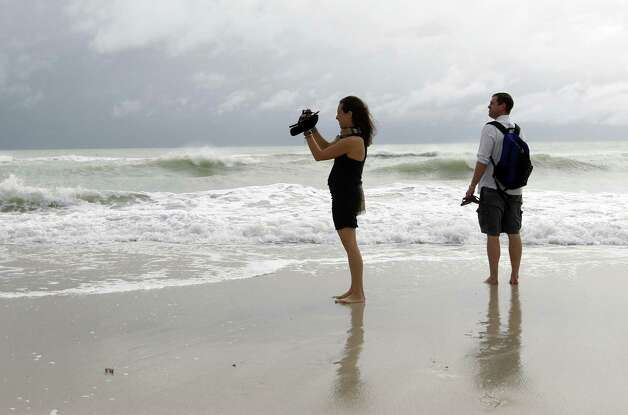 Tourists Stephanie and Dan Koch of Atlantic City, N.J. take a photograph of high surf as Hurricane Sandy passes offshore to the east, Friday, Oct. 26, 2012, in Miami Beach, Fla. Hurricane Sandy left at least 21 people dead as it moved through the Caribbean, following a path that could see it blend with a winter storm and reach the U.S. East Coast as a super-storm next week. Photo: Lynne Sladky, AP / AP