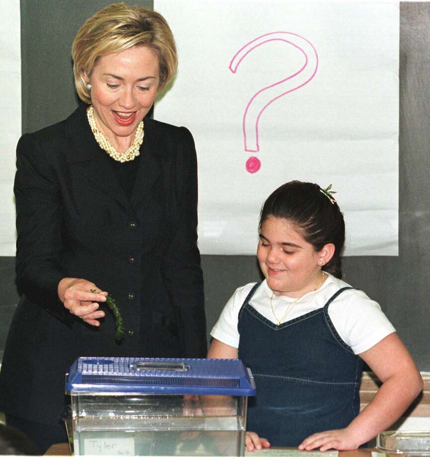 First Lady Hillary Clinton holds an aquatic plant eaten by frogs as she is given a demonstration about frogs by third-grader Chelsea DiGiovanni during a visit to Village Elementary School on April 20, 1999 in Syosset, N.Y. Photo: MATT CAMPBELL, Getty Images / AFP