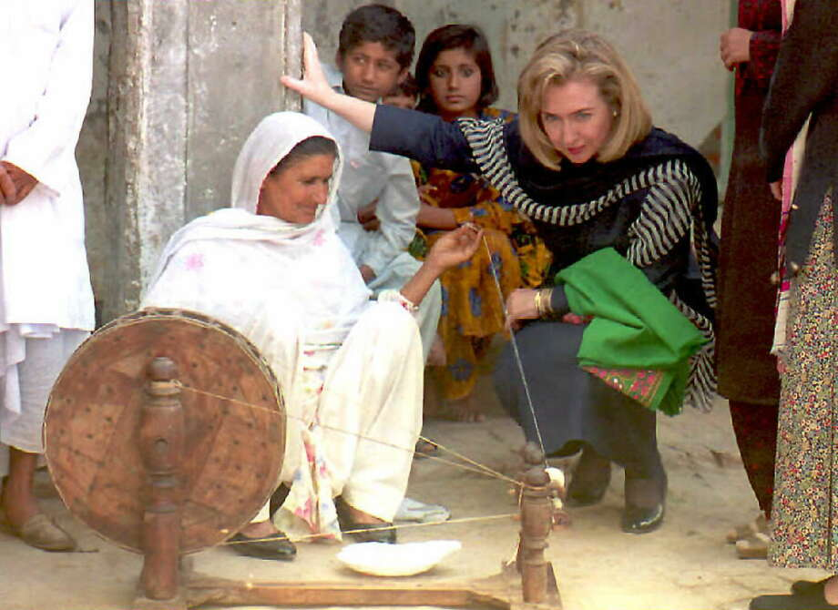 First Lady Hillary Clinton watches a local woman working on a traditional spinning wheel at Burki village near the Pakistan-India border. Photo: SAEED KHAN, Getty Images / AFP