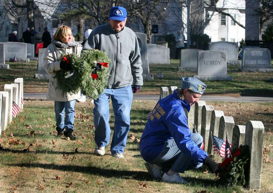 Barbara Totora, of the Catholic War Veterans of Bridgeport Post 1466, places a wreath on a veterans grave after a Wreaths Across America ceremony at the Mountain Grove Cemetery on Saturday, Dec. 12, 2009. The Bridgeport Elks hosted the event, which honors Veteran's laid to rest. Over 350 cemeteries across the country simultaneously held ceremonies. Photo: B.K. Angeletti / Connecticut Post