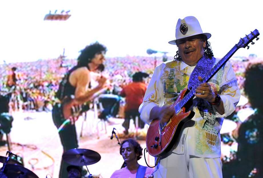 Santana, then and now: Oye como va? That's Carlos Santana performing in Bangalore during the first concert of his India tour. Behind the stage is an image of Santana at Woodstock in 1969.  Photo: Manjunath Kiran, AFP/Getty Images