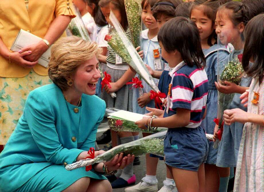 First Lady Hillary Clinton laughs as she is presented a bouquet of flowers by Japanee children July 8, 1993 at the Meguro waste incineration plant in Tokyo, Japan. Photo: DAVID NELSON, Getty Images / AFP