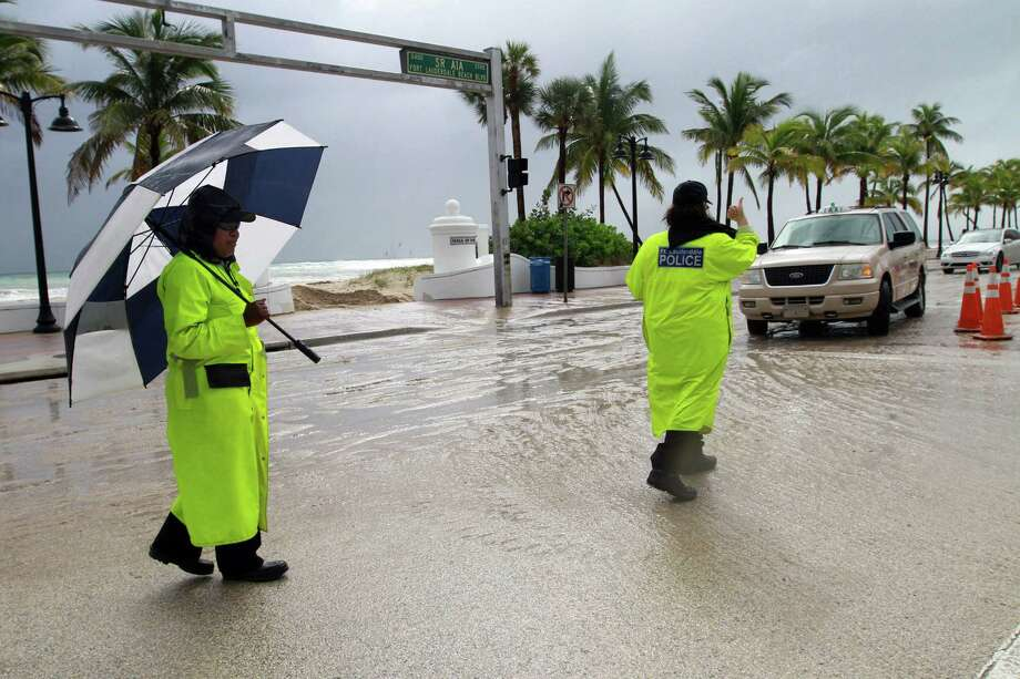 Ft. Lauderdale Police public safety aides Maggie Depasse, left, and Denise Melanson work traffic control on A1A at SE 5th Street for the Ft. Lauderdale International Boat Show on Ft. Lauderdale Beach, Friday, Oct. 26 amid stormy, sandy conditions as Hurricane Sandy passes to the east. Photo: Amy Beth Bennett, McClatchy-Tribune News Service / ARCHIVE