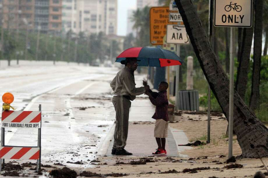 Thaddeus Hamilton, of Sunrise, left, holds an umbrella for his grandson Christian Hamilton, 6, of Lauderhill, as they check out sand and debris on the roadway on A1A between Sunrise Blvd. and NE 20th Street on Ft. Lauderdale Beach on Friday, Oct. 26. Photo: Amy Beth Bennett, McClatchy-Tribune News Service / ARCHIVE