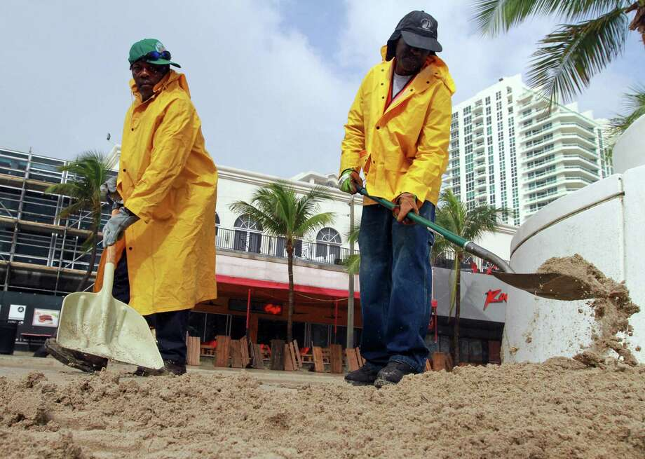 Ft. Lauderdale city workers Wisly Eliodor, left, and Rameau Toussaint shovel sand off of the sidewalk and back onto Ft. Lauderdale Beach on Friday, Oct. 26. Photo: Amy Beth Bennett, McClatchy-Tribune News Service / ARCHIVE