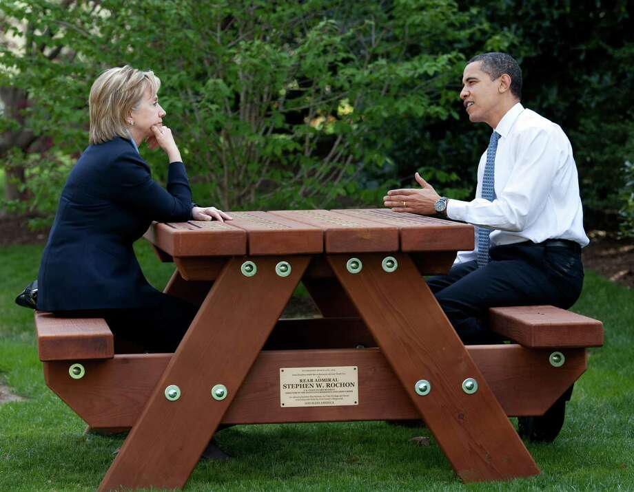 In this handout provide by the White House, U.S. President Barack Obama walks with Secretary of State Hillary Rodham Clinton speak together sitting at a picnic table on the South Lawn of the White House on April 9, 2009 in Washington, DC. Photo: The White House, Getty Images / 2009 White House