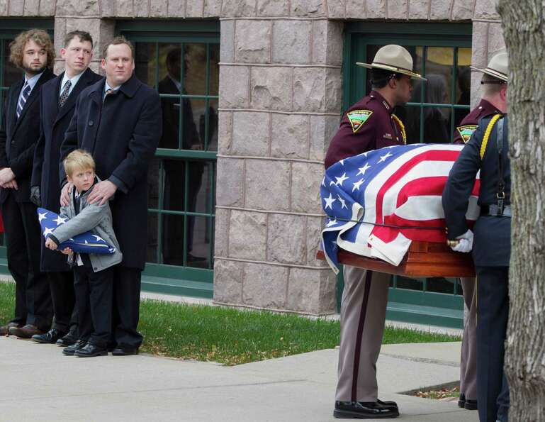 Will Mead holds a tri-folded flag as he watches with family members the casket of his great grandfat