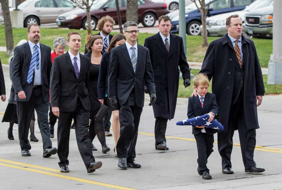 Great grandson Will Mead and his father Tim Mead, front, lead family members as they walk behind the hearse carrying the casket of former Democratic U.S. Senator and three-time presidential candidate George McGovern, on the way to the funeral Friday. Photo: Nati Harnik, Associated Press / AP