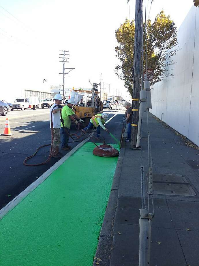 Workers install a green bike lane, intended to give bicyclists a place to ride that is protected from cars. Photo: Livable Streets