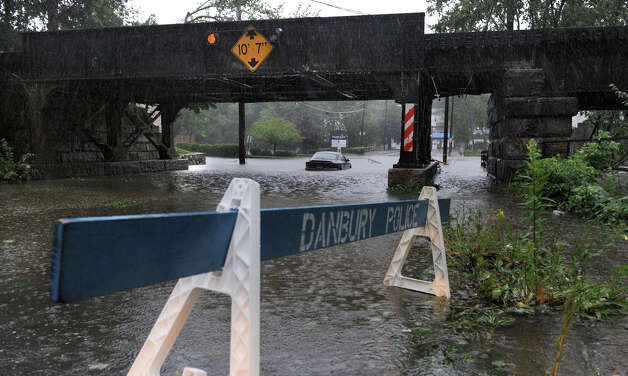A car is stuck in the fllood water under the West Street bridge in Danbury Sunday morning. Hurricane Irene is bringing heavy rains and wind to the area. Photo: Carol Kaliff
