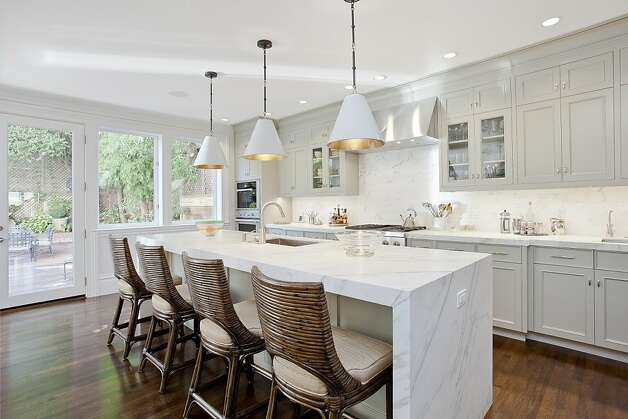 The contemporary kitchen includes an 11-foot long island featuring Calacatta D'orro premium marble. Photo: OpenHomesPhotography.com
