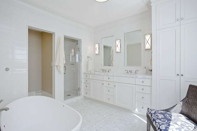 The master bathroom offers dual sinks, a large tub, a separate shower stall and room for a sitting area. Photo: OpenHomesPhotography.com