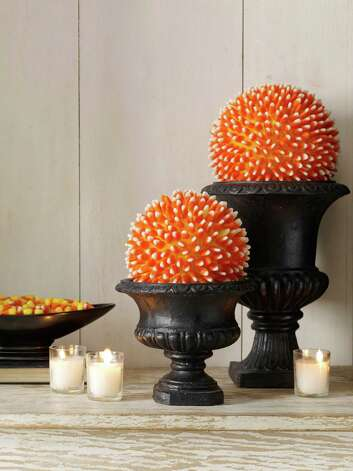 This candy corn centerpiece can be created using a hot glue gun, a bag of candy corn and a Styrofoam ball or cone shape. Instructions are available at www.womansday.com. Photo: Antonis Achilleos, Associated Press / Woman's Day