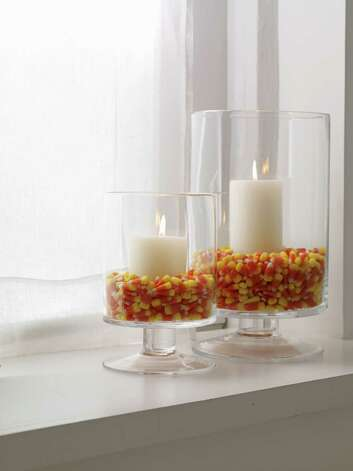 Glass hurricanes filled with candy corn and  pillar candles are an interesting display. Photo: Antonis Achilleos, HONS / Woman's Day