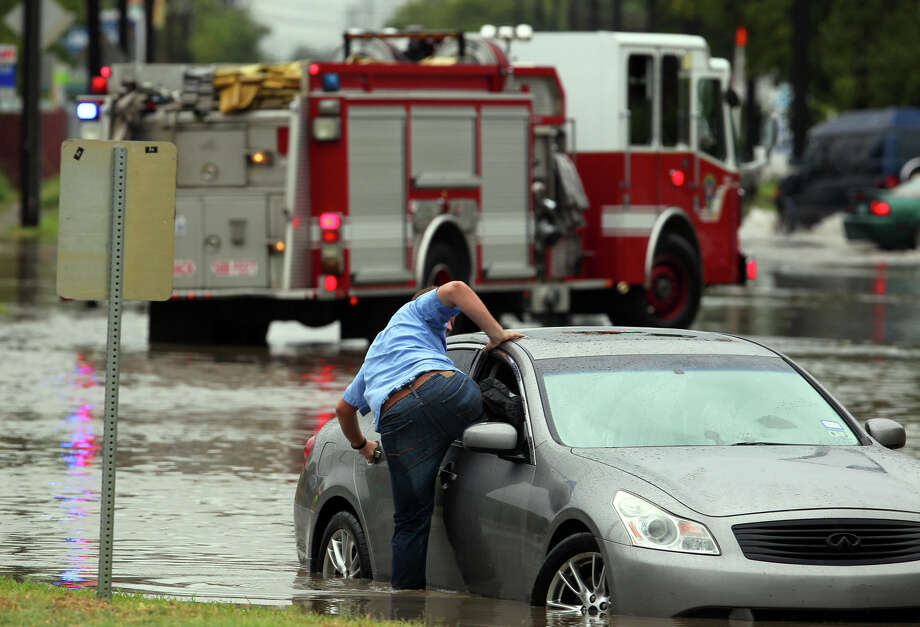 Chris Scharnhorst extricates himself from his flooded car after he got stuck in high water shortly after noon on the 1,000 block of Quintana Road near Port San Antonio after rain swept through the San Antonio area Friday October 26, 2012. Scharnhorst, a Boeing employee, said he was on lunch break when cars in front of him slowed down and large trucks passed by creating large wakes of water. The large volume of water caused his car to stall, prompting rescue calls to the fire department. Firefighters and police urged him to leave his car, but San Antonio police patrol officer John Doporto said Scharnhorst would not leave his car. After the rain let up and after more urging from Doporto, Scharnhorst climbed out of his car. Doporto said Scharnhorst would not be fined because there were no barriers in place when his car stalled. / ©San Antonio Express-News/Photo Can Be Sold to the Public