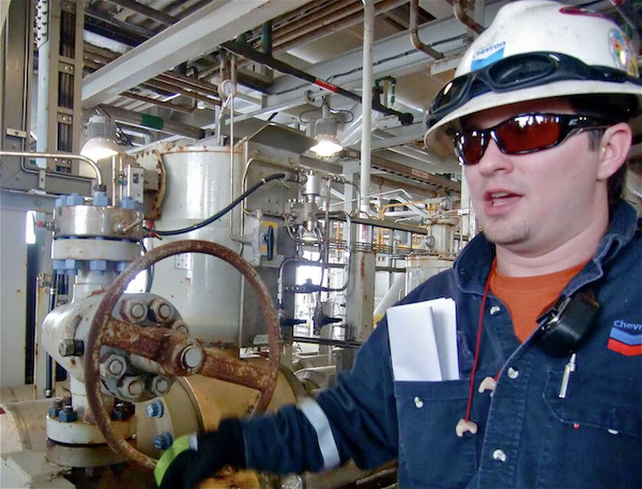 Chuck Harrison, field operator, explains the shut-in valve that safely stops the flow on Chevron's Tahiti platform in an emergency. (Simone Sebastian/Houston Chronicle)