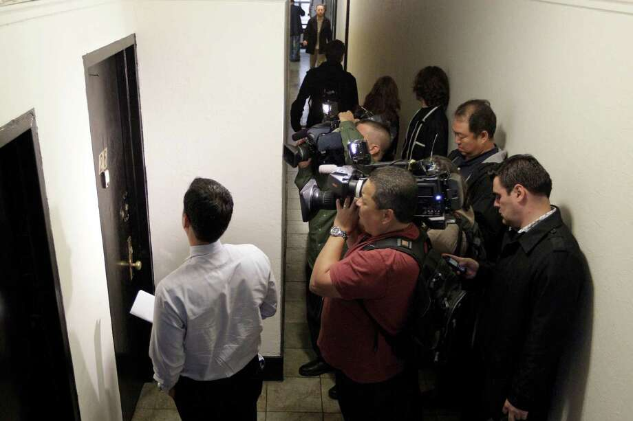 Reporters surround the apartment door of Yoselyn Ortega, the nanny suspected of killing two children in her care, Friday, Oct. 26, 2012 in New York. Ortega was in critical condition Friday with apparently self-inflicted injuries. The children's mother returned home Thursday evening to find two of her small children dead in a bathtub and Ortega, with self-inflicted stab wounds, lying near them, police said. (AP Photo/Mary Altaffer) Photo: Mary Altaffer, STF / AP