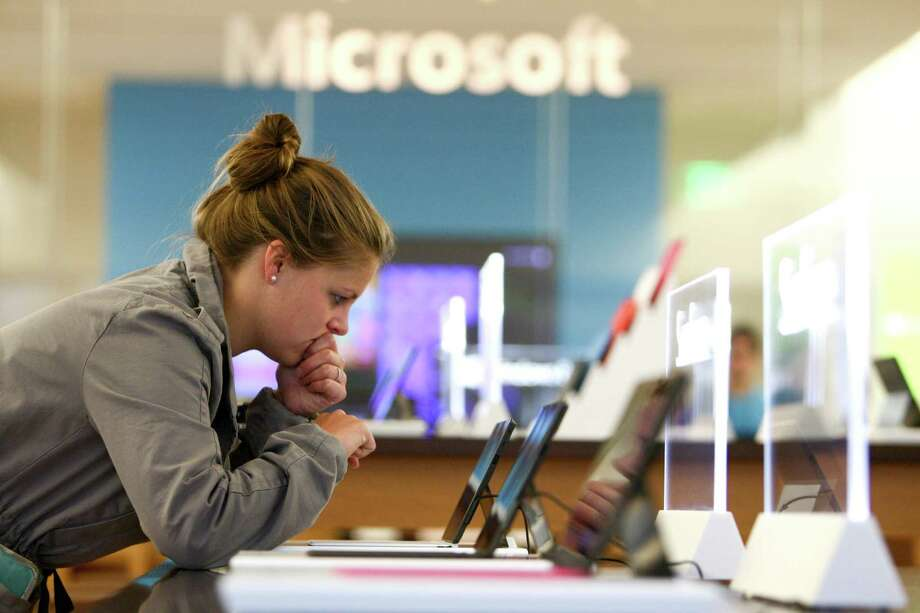 Peri Erickson-Brown looks over a Microsoft Surface as Microsoft's new Surface tablet computer is released on Friday, October 26, 2012 at the University Village Microsoft Store in Seattle. Photo: JOSHUA TRUJILLO / SEATTLEPI.COM