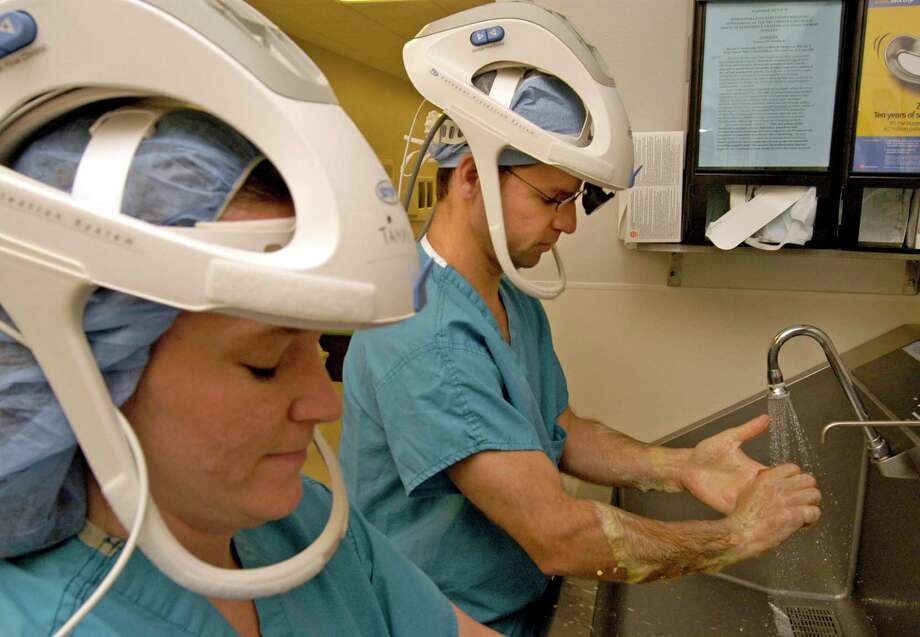 Dr. Kelly Blevins, right, an orthopedic surgeon and Tammy Drerup, an orthopedic physician's assistant, scrub up before surgery at Memorial Herman Hospital wearing helmets to support their surgical suits. The suits are designed to prevent spreading infections. Photo: Johnny Hanson, FREELANCE / FREELANCE