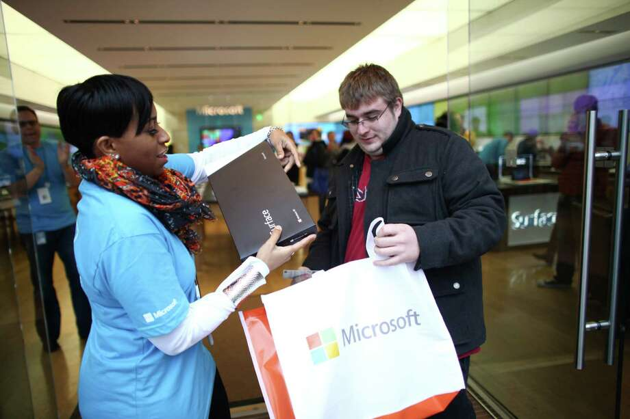 Cole Lummus, who had been waiting since 10 p.m. the previous day, leaves with a new Surface as Microsoft's new Surface tablet computer is released on Friday, October 26, 2012 at the University Village Microsoft Store in Seattle. Photo: JOSHUA TRUJILLO / SEATTLEPI.COM