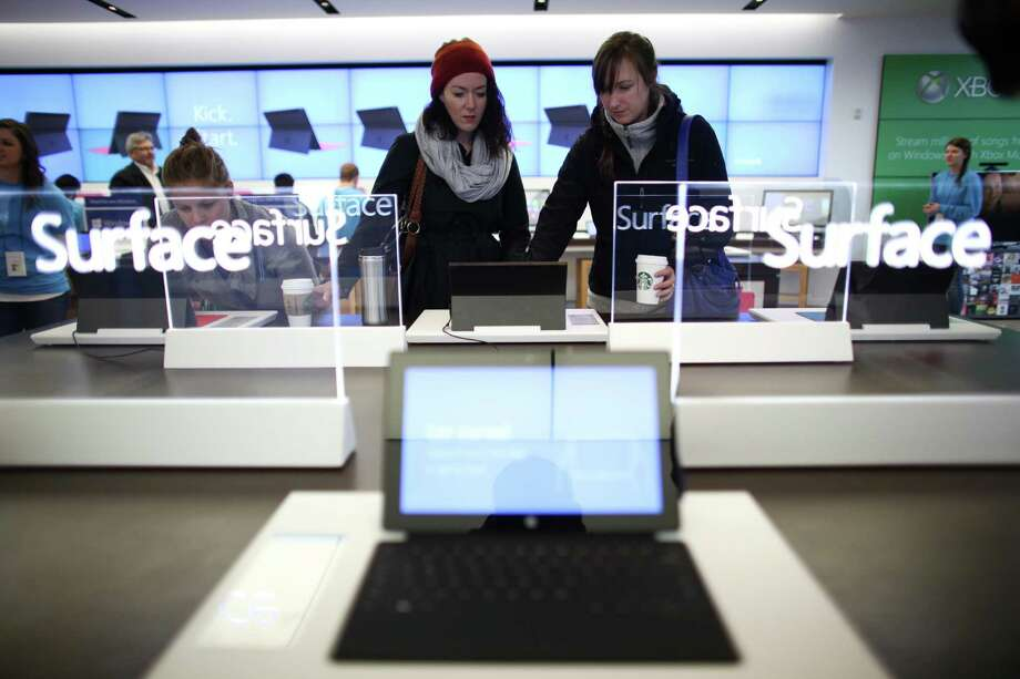 People look over a Surface as Microsoft's new Surface tablet computer is released on Friday, October 26, 2012 at the University Village Microsoft Store in Seattle. Photo: JOSHUA TRUJILLO / SEATTLEPI.COM