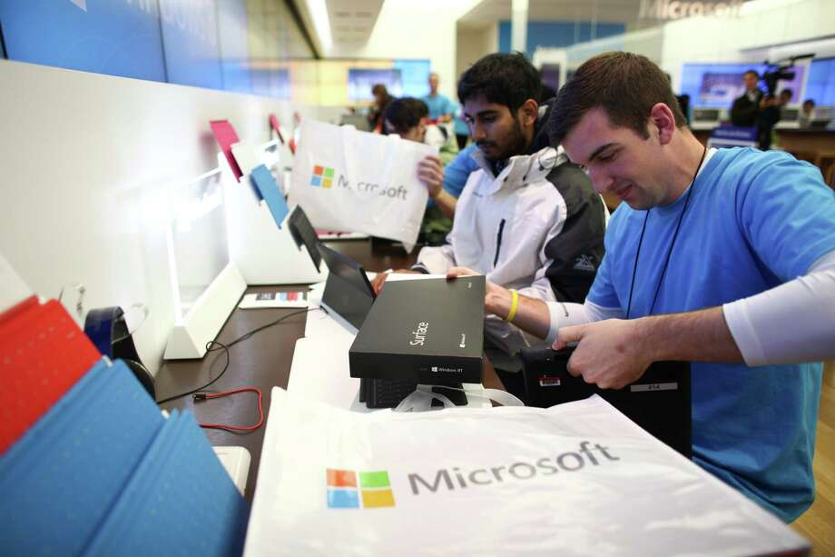 Microsoft Store employee Chad Robinson helps Naresh Bohjja as he purchases a new Surface as Microsoft's new Surface tablet computer is released on Friday, October 26, 2012 at the University Village Microsoft Store in Seattle. Photo: JOSHUA TRUJILLO / SEATTLEPI.COM
