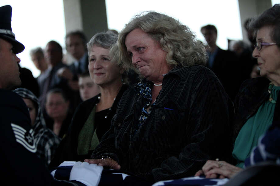 Lea Ann McCann (center), the daughter of Airman 1st Class Jerry Mack Wall, receives a flag from Tech. Sgt. David Teets, a member of the Lackland Honor Guard, during the service at Fort Sam Houston National Cemetery. McCann was seated between Wall's sister Karen Sue Casey (left) and Wall's mother, Lora Wall. Photo: Lisa Krantz, San Antonio Express-News / San Antonio Express-News