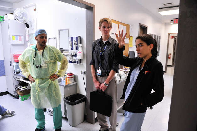Winston Faltine (from left), Elan Lee and Sanam Safahieh — dental students at the University of Texas Health Science Center — discuss the plans for a new $95 million oral health care center. Photo: Robin Jerstad, For The Express-News