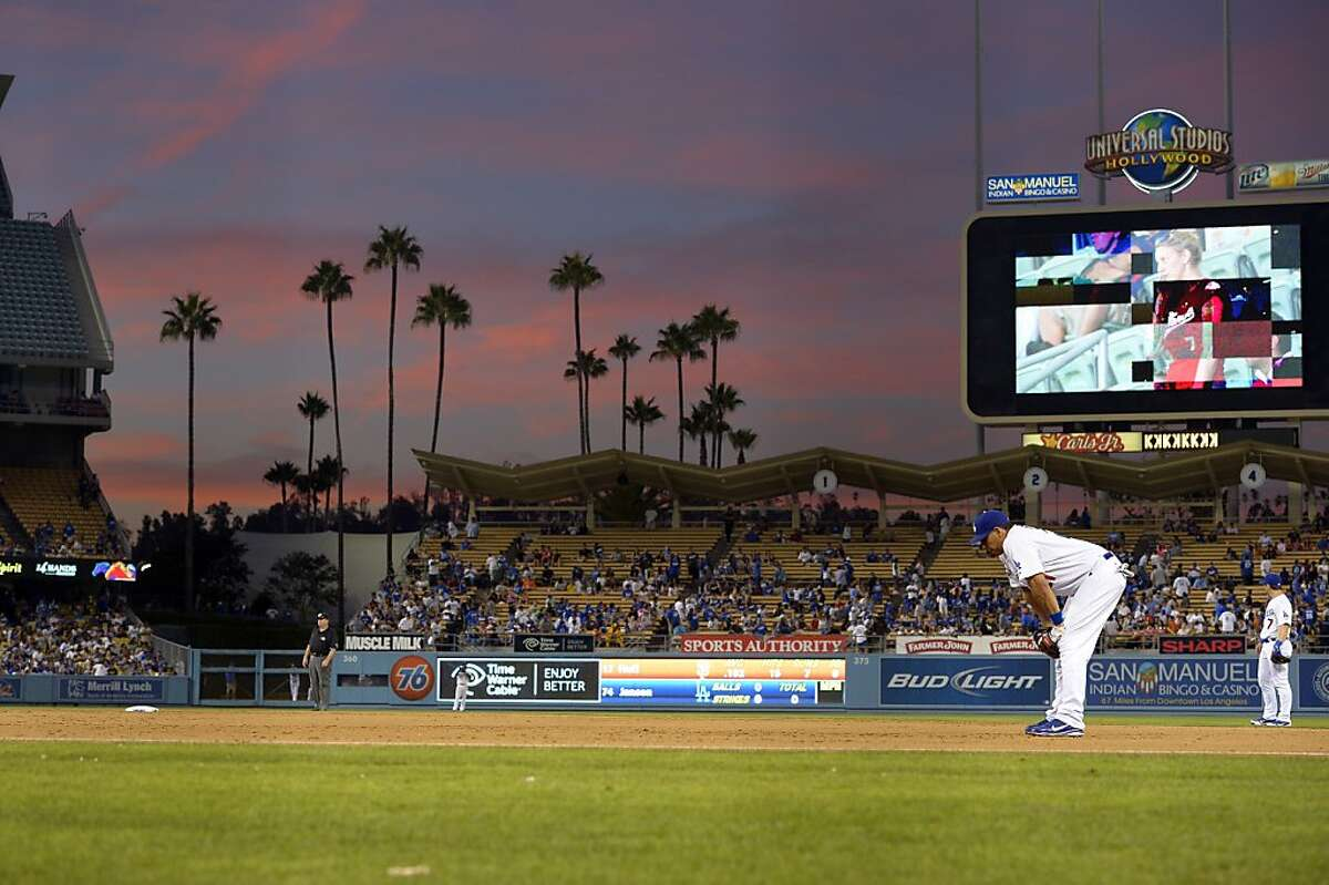 Los Angeles Dodgers first baseman Juan Rivera, second from right, and third baseman Nick Punto stand on the field as the sun sets during the ninth inning of their baseball game against the San Francisco Giants, Wednesday, Oct. 3, 2012, in Los Angeles. (AP Photo/Mark J. Terrill)