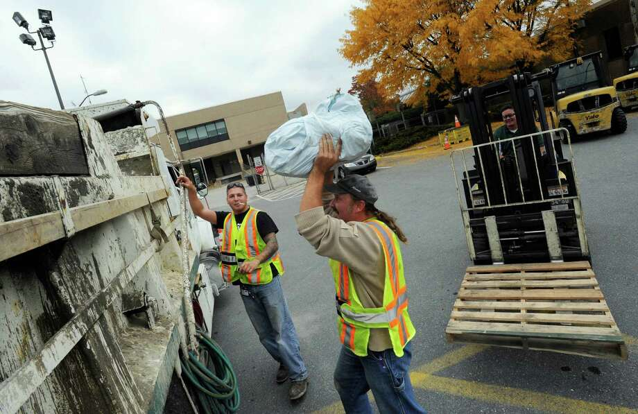 With Hurricane Sandy approaching, Baltimore utility workers Jordan Sauer, left, and William MacAleese, make ready by loading plastic bags for use as sand bags.  Photo: Steve Ruark, FRE / FR96543 AP