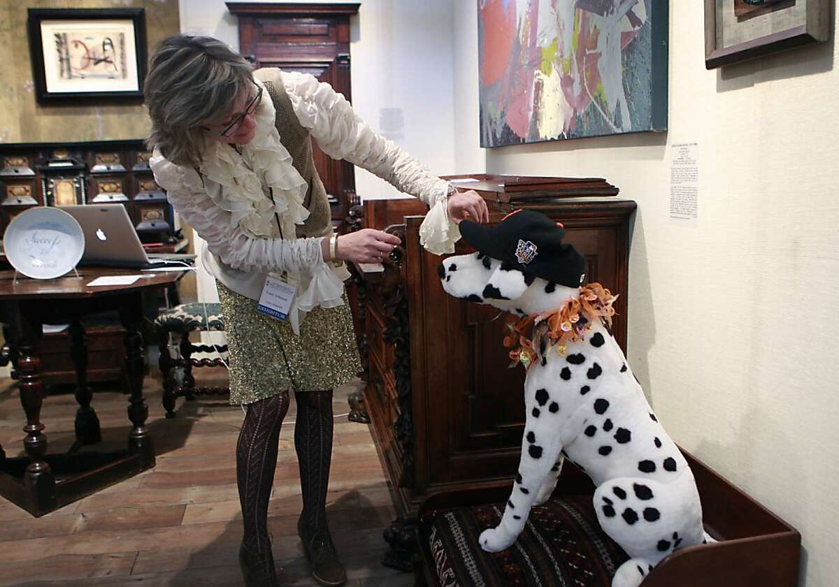 To get into the spirit of the Giants' amazing post-season success, Lucy Johnson adjusts a Giants baseball cap on a lifesized toy dog decorating an $8,000 dog bed at an antiques show at Fort Mason in San Francisco, Calif. on Friday, Oct. 26, 2012.