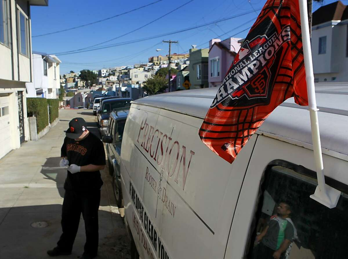 Ray Willis flies a National League championship flag from his van and wears Giants gear during his job as a plumber in San Francisco, Calif. on Friday, Oct. 26, 2012.