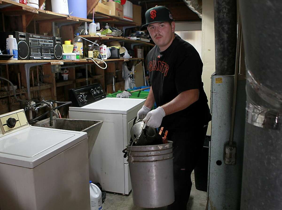 Plumber Ray Willis is decked out in Giants apparel as he clears a drain for a customer in San Francisco, Calif. on Friday, Oct. 26, 2012.