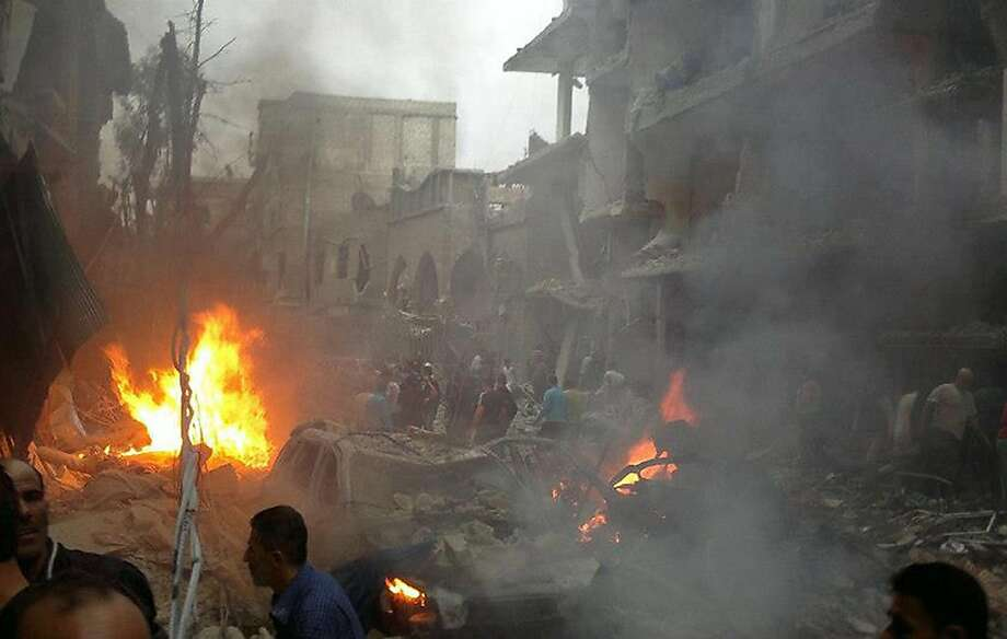 A handout picture released by the Syrian Revolution General Commission (SRGC) shows Syrians inspecting the site of a car bomb attack in the Daf Shawk district of Damascus on October 26, 2012. At least five people were killed and 32 wounded in a car bomb attack in southern Damascus, Syrian state television said, while the Syrian Observatory for Human Rights said children were among the wounded. Photo: Ho, AFP/Getty Images