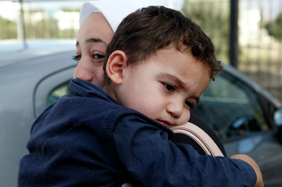 Two-year-old Bushr Al Tawashi, with his mother, Arin Al Dakkar, outside of a Sigma TV station in Nicosia, Cyprus, on Friday, was thought to be dead after his family inadvertently left him behind when they fled shelling in Damascus. Photo: Petros Karadjias, STF / AP