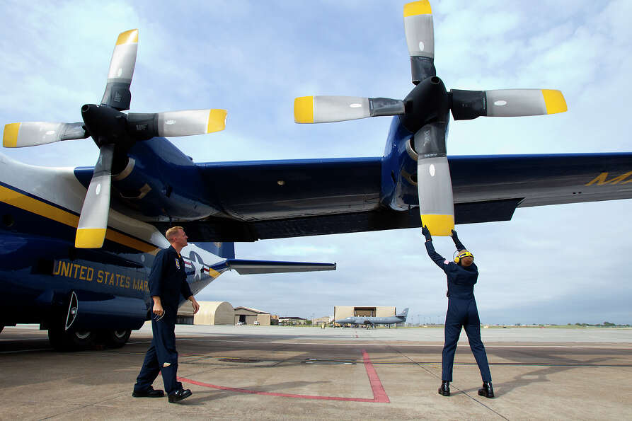 Marine Blue Angels Gunnery Seargeant Micah Bachtold, left watches as Staff Seargeant Adam Miller sto
