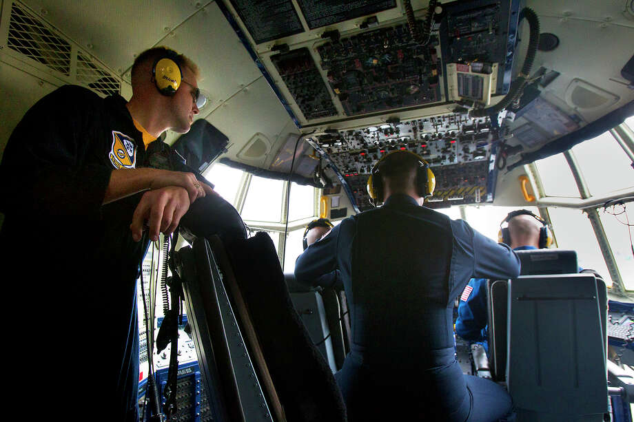 Marine Blue Angels, Gunnery Seargeant Micah Bachtold, left and Staff Seargeant Kevin Sanchez, center, watch as Captains A.J. Harrell and John Hecker fly the Blue Angel's Fat Albert C130 airplane at Ellington Field Friday, Oct. 26, 2012, in Houston. Photo: Cody Duty, Houston Chronicle / © 2012 Houston Chronicle