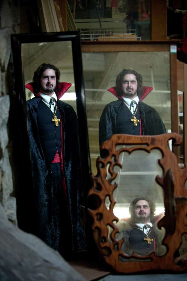 "Mike Jauregui models a ""vampire"" costume in front of vintage mirrors from Value Village.Cape – $9.99Shirt – $5.99Necklace – $4.99Pants – $6.99About $28 Photo: JOSHUA TRUJILLO / SEATTLEPI.COM"