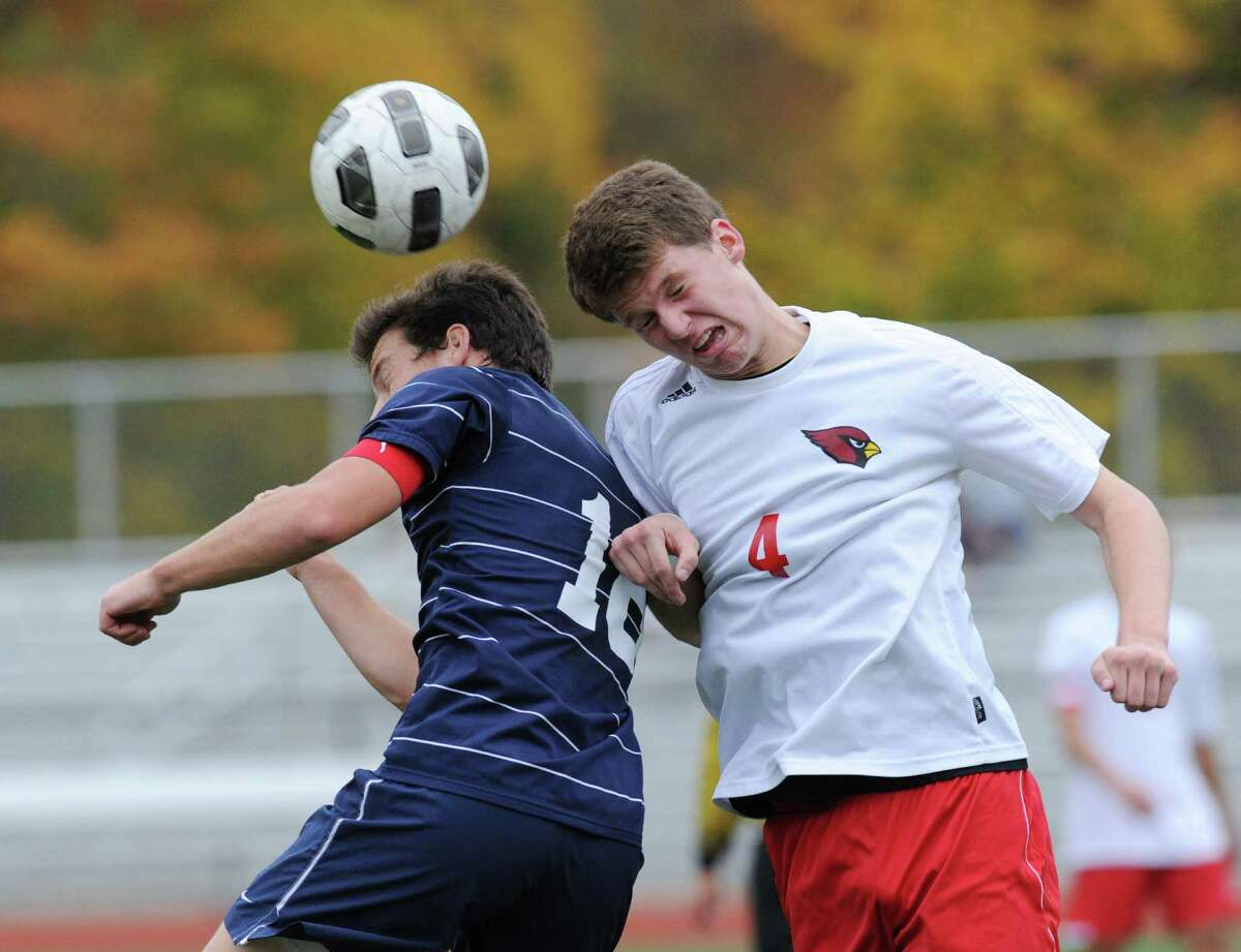 At left, Joseph Greenwald # 16 of Staples heads the ball along with Will Gittings of Greenwich during the FCIAC boys soccer quarterfinal match between Staples high School and Greenwich High School at Greenwich, Friday afternoon, Oct. 26, 2012. Greenwich advanced with a 3-0 win.