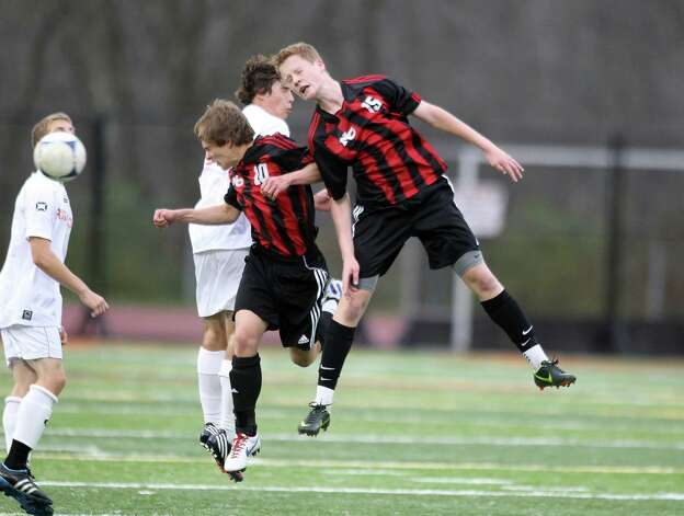 New Canaan soccer captain Stephen Valante and teammate Alex Robey react to a head ball situation  during FCIAC soccer action against Ridgefield on Friday night. Photo: J. Gregory Raymond