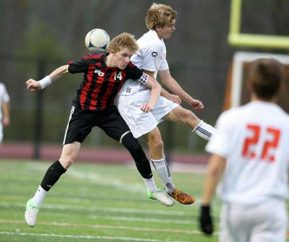 New Canaan soccer captain Marcus Hijkoop battles for a header with Ridgefield's John Findlay during  FCIAC soccer action in Ridgefield on Friday night. Photo: J. Gregory Raymond