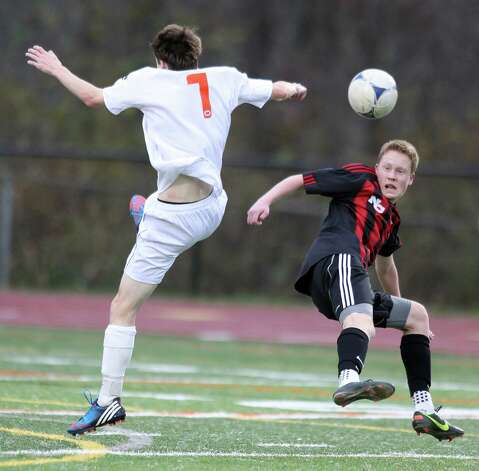 Ridgefield player Daniel Standish and New Canaan's Jack Ludtke battle for a loose ball during soccer action in Ridgefield on Friday evening. Photo: J. Gregory Raymond